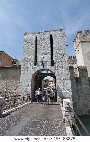 Sirmione, Italy - June 10 - 2016: Tourists come into Sirmione through the castle gate