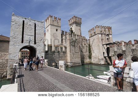 Sirmione, Italy - June 10 2016: Tourists come into Sirmione through the castle gate