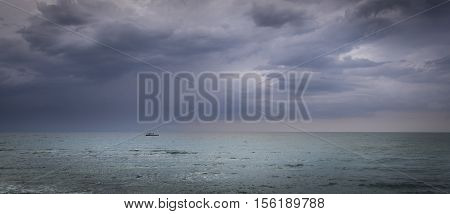 Sailboat in open sea and astorm approaching dramatic skies calm sea