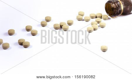 still life of pills over white table with brown glass bottle. pharmaceutical. disease remedy