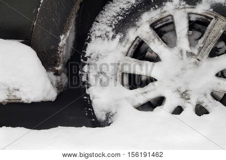 Closeup of a car wheel trapped in snow, outdoor cropped shot