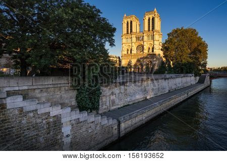 Notre Dame de Paris cathedral at sunset with the Seine River on Ile de La Cite. Summer evening in the 4th Arrondissement, Paris, France