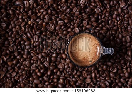 a cup of espresso coffee on coffee beans background