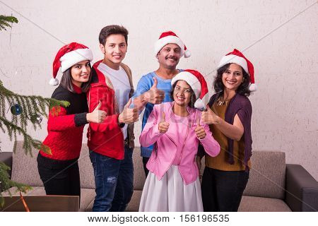 family, happiness, generation, holidays and people concept - happy indian family in santa helper hats standing and showing thumbs up gesture at home, indian family and christmas