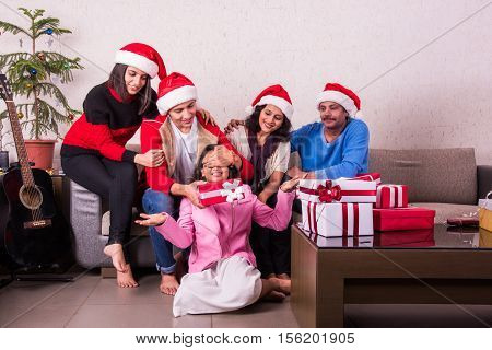 family, christmas, holidays and people concept - happy indian family with gift boxs sitting on sofa or couch at home, Indian family celebrating christmas, merry christmas