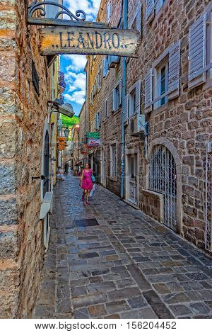 BUDVA, MONTENEGRO - JULY 18: Unknown people walking on picturesque narrow street, on July 18, 2014 in Budva, Montenegro. Budva among the oldest urban settlements of the Adriatic coast, a UNESCO World Heritage Site.