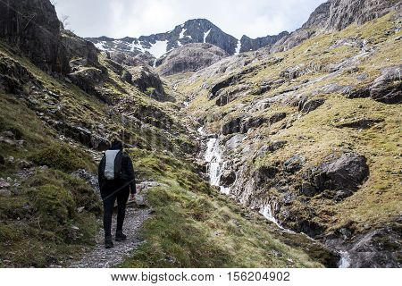 Glen Coe Highlands scotland girl hiking in nature uphill crossing waterfall for panorama view 3