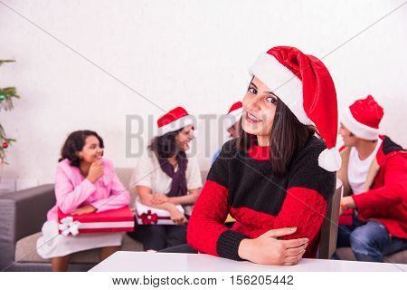 indian young and beautiful girl with red santa hat, sitting on table close to camera and family sitting on sofa in the background with christmas tree, Indians celebrating christmas, 25 december, merry christmas