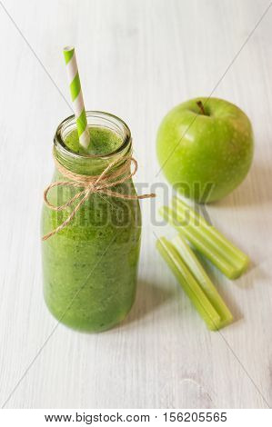 Healthy celery smoothie with green apple in bottle. Green smoothie for weight loss and detox selective focus vertical