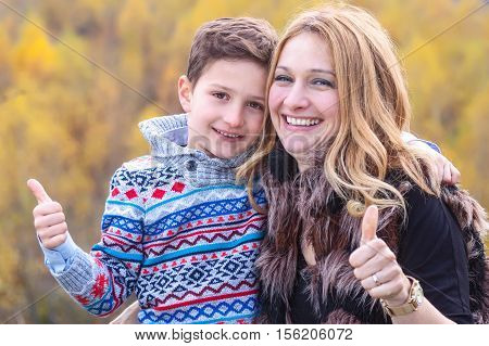 Mother and son showing ok sign stand outdoors in nature