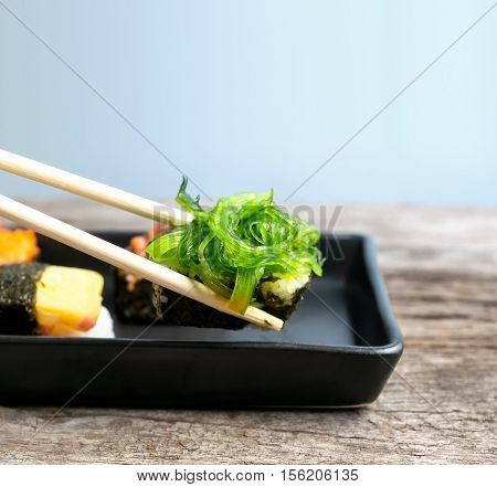 Close Up Of Chopsticks Taking Portion Of Sushi Roll On The Table Restaurant / Eating Sushi Roll Usin