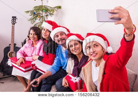 family, holidays, generation, christmas and people concept - smiling indian family with camera/smartphone taking selfie, sitting on sofa with christmas tree, background, christmas celebration in india