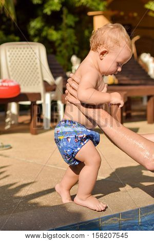 Toddler Child Goes To The Hands Of His Father To The Pool