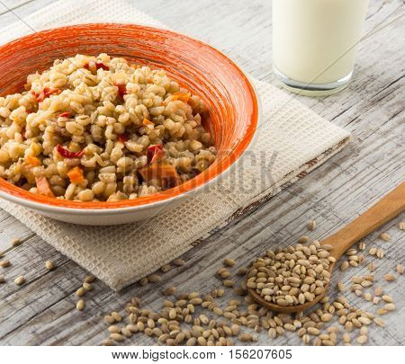 Pearl barley porridge with vegetables in an orange ceramic plate with a kitchen towel pearl barley in a wooden spoon and glass of milk on a white wooden table