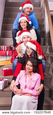family, christmas, holidays and people concept - happy indian family with gift box sitting on staircase or steps indoors, indian family celebrating christmas, merry christmas