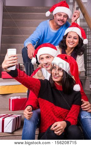 family, holidays, generation, christmas and people concept - smiling indian family with cameraor smartphone taking selfie and sitting on steps or stair case