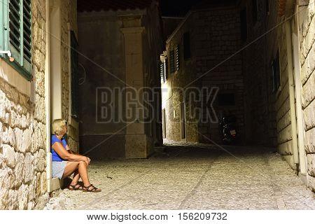 Women sitting in a dark alley picture from Postira city on Brac Island in Croatia.