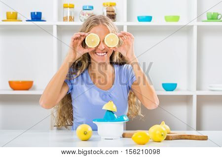 Beautiful girl is covering her eyes with slices of lemon while making lemonade.