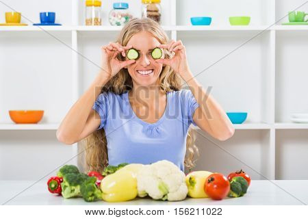 Beautiful girl is covering her eyes with slices of cucumber and sitting at the table with bunch of vegetable.