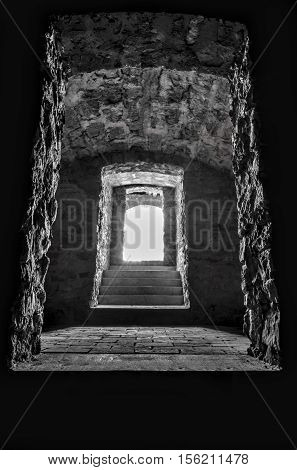Sunlight at basement entrance - Black and white image of interior of an old basement with the sunlight's coming through the door over the stone walls and floor