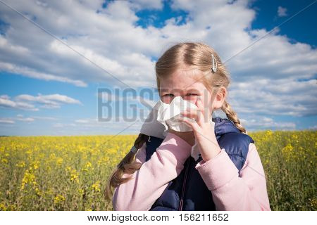 Young girl blowing her nose, possibly because of an allergy