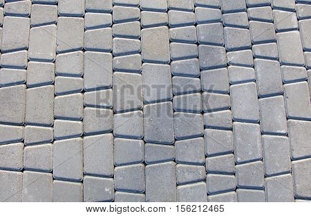 Background of gray paving stones road. Abstract structured background of modern street pavement slabs pattern