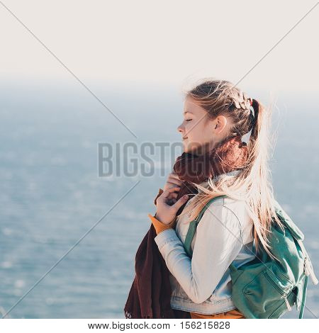Smiling teen girl 14-16 year old traveling with backpack over sea background. Wearing warm scarf knitted sweater and denim jacket.