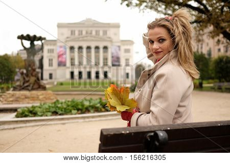 attractive young woman with colour leaves outdoors smiling closeup portrait
