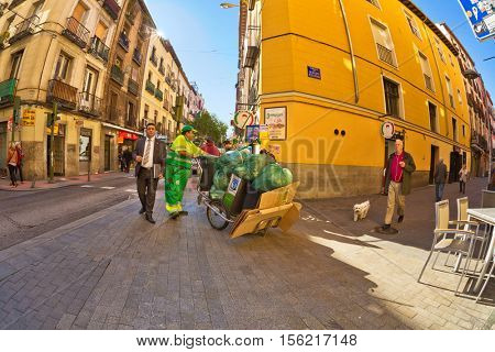 MADRID, SPAIN - NOVEMBER 11, 2015 : Scavenger driven truck with garbage on the intersection of the main pedestrian streets in the neighborhood of Chueca in central Madrid