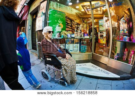 MADRID, SPAIN - NOVEMBER 11, 2015 : An elderly woman in a wheelchair in the street in front of the small shop in the neighborhood of Chueca in central Madrid