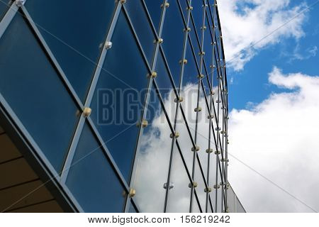 background glass office building windows with reflection of sky in them