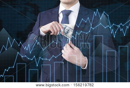 Close up of businessman putting dollar bills in jacket's inner pocket. There are graphs in the foreground and a world map in the background. Double exposure.