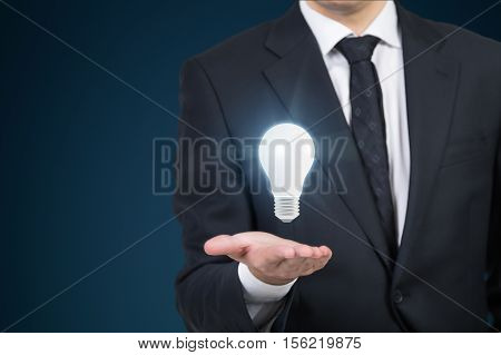 Close up of a businessman in dark suit who has a light bulb floating above his hand. Concept of a brilliant idea. Mock up
