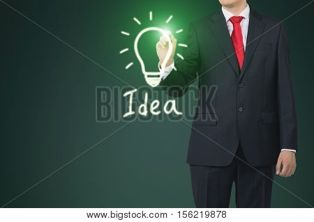 Close up of a businessman wearing a red tie and drawing a green glowing light bulb sketch on a glassboard. Mock up.