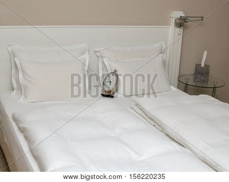 Clock On Pillows On A Bed