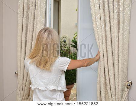 Lady Opening Window
