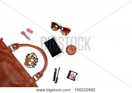 Contents of female handbag - sunglasses, makeup items, smartphone, trendy jewellery, flat lay