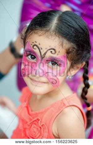 Portrait of a four year old cute pretty girl child young with her face painted for fun at a birthday party