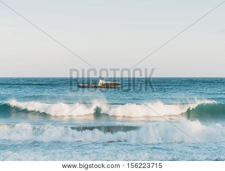 Boat in the sea at windy weather sea waves with foam