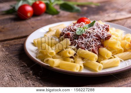 Pasta with tomato sauce and parmigiano on natural wooden table.