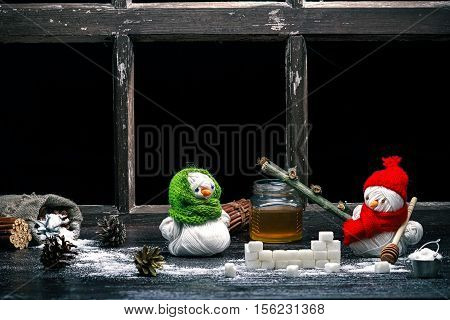 Handmade toy snowman and snowgirl of yarn skeins making stove of sugar and honey over black background. Color toning