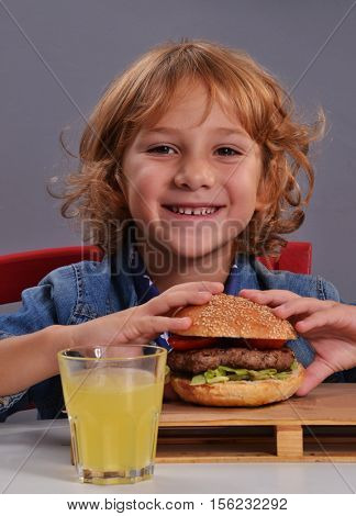 Funny kid eating burger and drinking orange soda.Child eating burger.