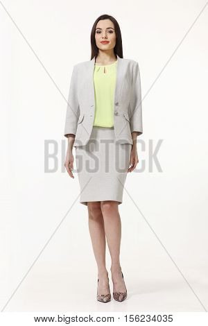 woman with straight hair style in two pieces jacket and skirt suit high heels shoes full length body portrait standing isolated on white
