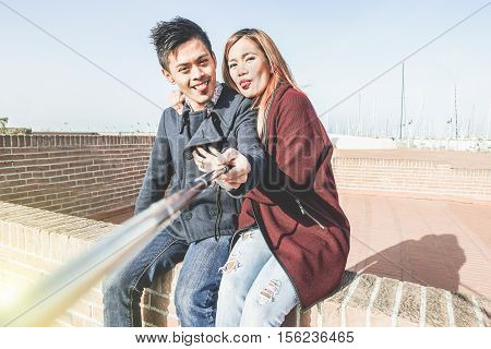 Asian young couple taking selfie with smart phone for vacation in europe next harbor - Happy people making funny faces on phone camera for souvenir photo - Happiness and love concept - Warm filter
