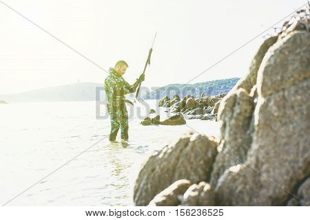 Male hunter getting ready for hunting wearing camouflage weatsuit with back sunlight - Young man preparing speargun for underwater fishing - Extreme sport concept - Soft warm desaturated filter