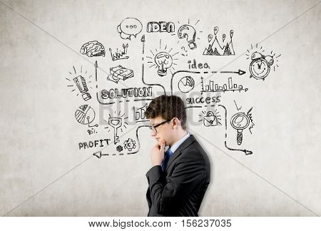 Side view of a bespectacled businessman who is thinking while standing near a concrete wall with business sketches on it. Concept of strategy in business