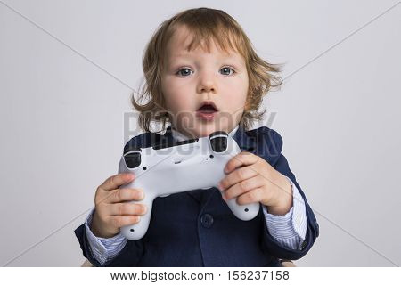 Surprised little boy holding a game controller and looking to the camera. Concept of gaming