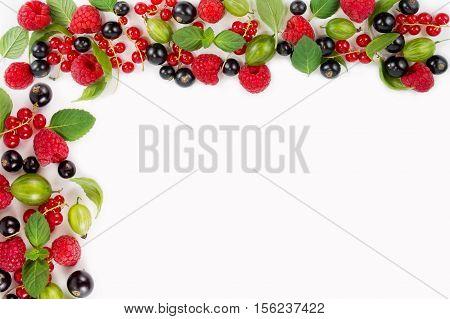 Various fresh summer berries. Ripe raspberries currants gooseberries mint and basil leaves. Berries on white background.
