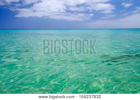 Transparent emerald sea water and blue sky.