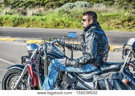 biker on a classic motorcycle on the edge of the road